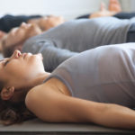 Group of young people in yoga lesson, lying in corpse pose