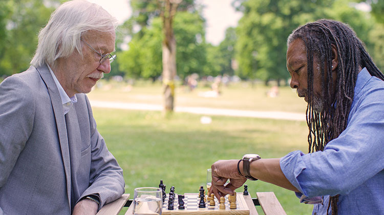 Senior men playing chess outdoors