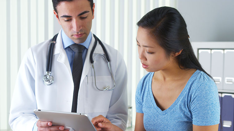 Patient talking with doctor while they look at tablet together