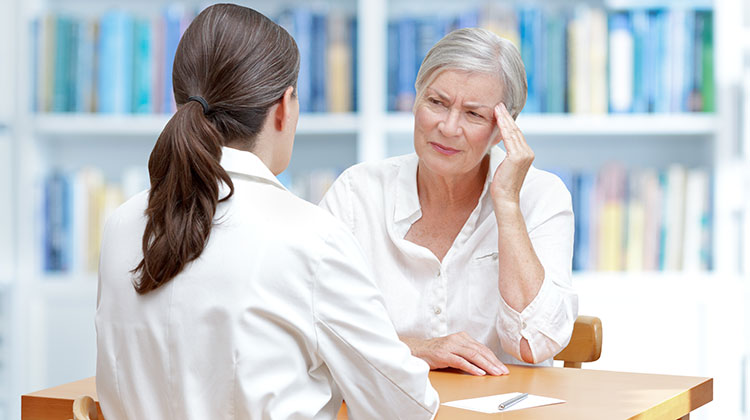 Senior patient with headache talking to her doctor