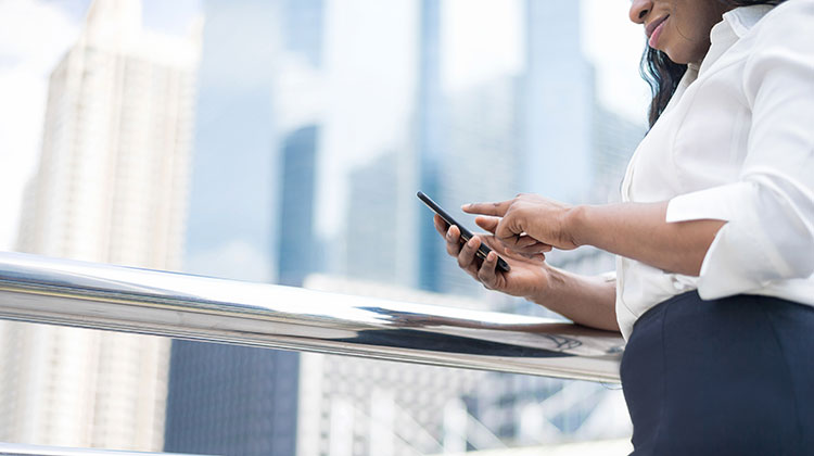 Professional woman outdoors typing on mobile phone