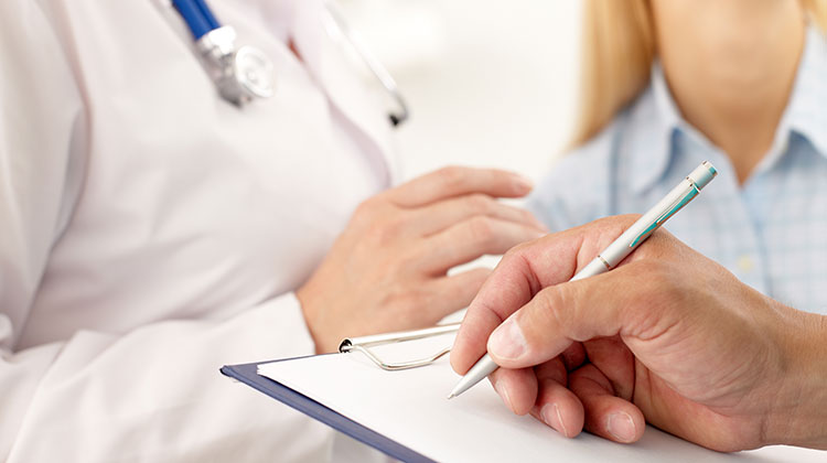 Closeup of taking notes while doctor meets with patient